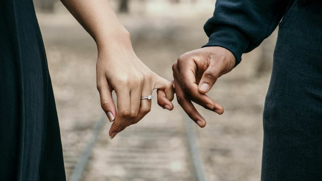 two hands hold each other